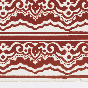 Red-flocked scalloped border with scrolls and dots, all on a polished or satin white ground. PRinted three across.