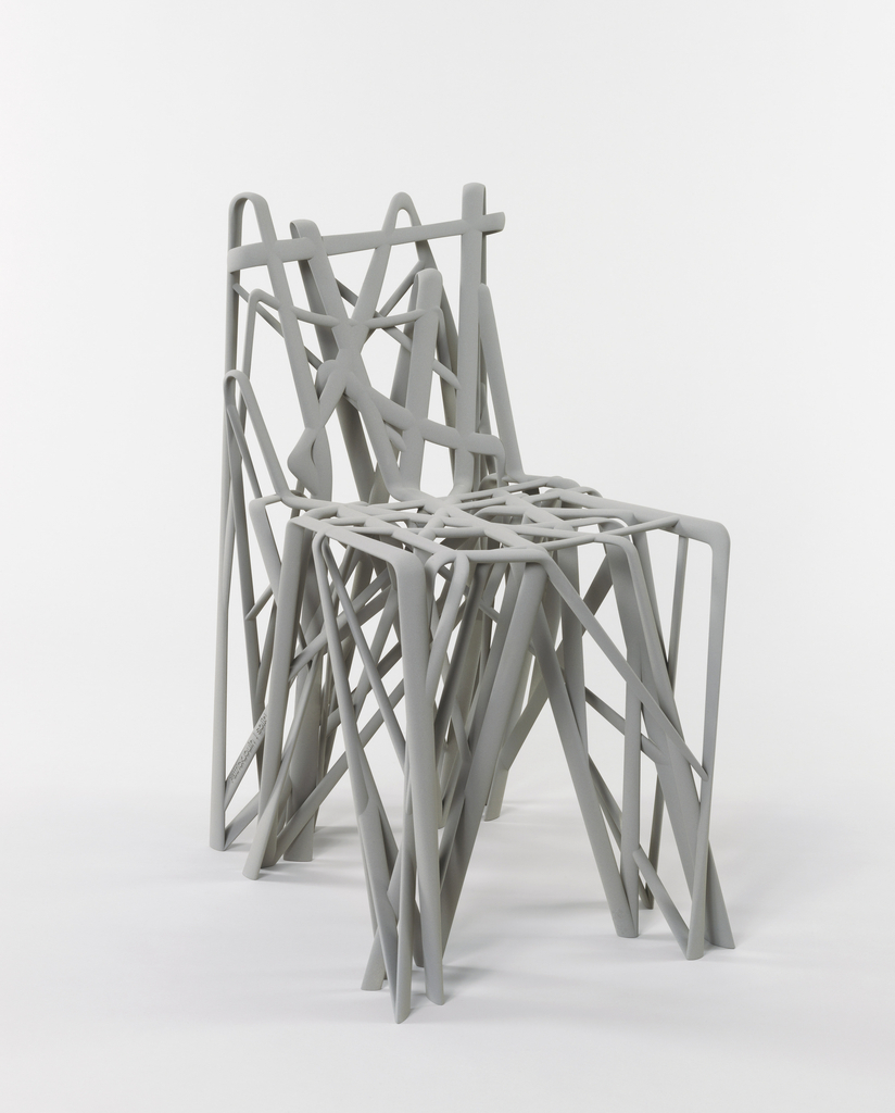 Gray, single-piece form of vertical, horizontal and diagonal elements reminiscent of bent and overlapping blades of grass shaped to form the back, seat, and legs.