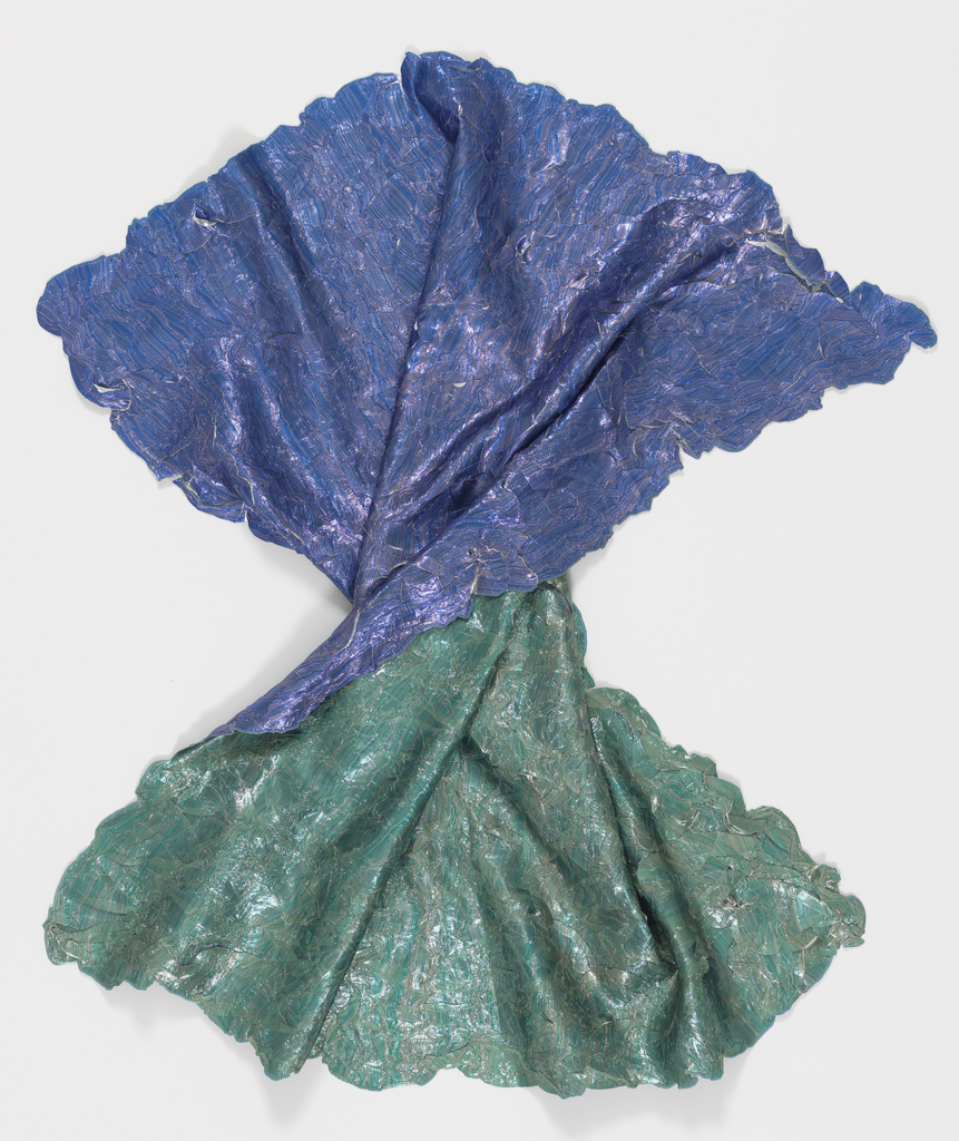 Square metallic scarf, printed in blue on one side and green on the other, with small folds and creases all over which reveal the silver color of the foundation fabric  when stretched or opened.
