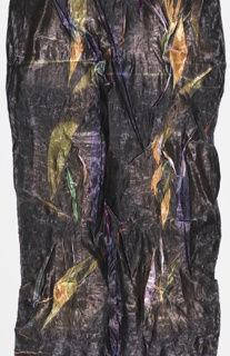 Length of fabric with overall random creasing. The outer surface has a dark metallic sheen, but inside the creases the fabric is multicolored with silver metallic. Warm palette of oranges and yellows on one side, a cooler palette of purples on the reverse.
