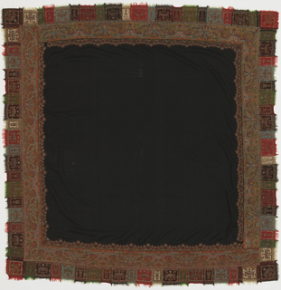 Square shawl with a black center on a field made to be folded on a diagonal and worn as a triangle. Inner border of Kashmir woven strips. Outer fringed border is patchwork and embroidery of decent quality.