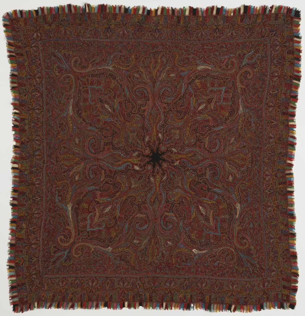 Square multicolored shawl with a patchwork border of small fringed pieces has a small black star-shape in the center.