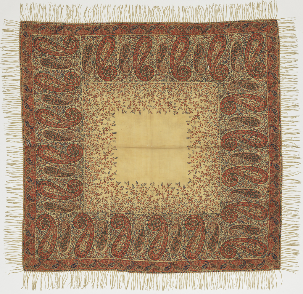 Square cream-colored shawl printed in strong shades of pink, blue, green, and brown with a deep border of large, stylized paisleys on a ground of close-set flowering branches; more trees rise from these into field. Paisley and floral guard borders.
