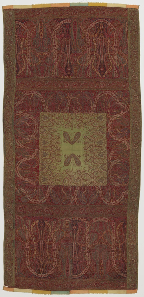 Shawl with large-scale leaves. Center in light green with repeated almond shapes in pairs surrounded by floral elements. Center enframed by four outer borders of varying widths. Predominantly red and green.