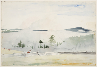 Horizontal view of a landscape with morning haze showing a fence with three deer in the foreground, tree tops and smoke in the middleground, and mountains in background.