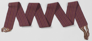 Belt patterned with thin stripes in shades of mauve and pink predominantly, also black, yellow, orange, and green. Both ends have warp fringes. Weft ribbing from heavy cerise wefts.