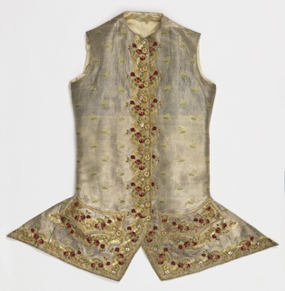 Waistcoat of silver cloth brocaded in a small flower pattern with a two and half inch border, woven in one with the cloth. Metal is bound in twill weave. Border is an elaborate combination of chenille and three kinds of fine gold cord. Design is small red roses and green foliage in chenille intertwined with a meander of gold, and ornament in meander of raised loops. Flower heads of foil outlined in fine gold bullion stitches; outline of parts of the design, of front of waistcoat, and of pockets in fine threads of gold paillettes. Form of waistcoat is slightly fitted at waist, and at bottom, corners sweep back to point. Closes from neck to point; where coat sweeps back, in twelve foil-covered buttons. No collar. Pockets shaped into side and center points of same weave as border design, and with three buttons. Back, satin, laced; lined with satin throughout. Pockets of white leather.