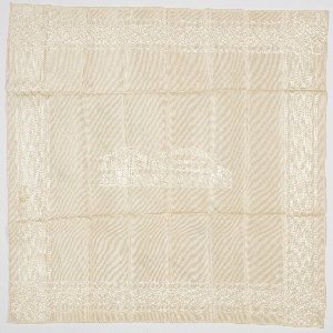 White-on- white handkerchief depicting the Brooklyn Bridge with boats and the surrounding cityscape. The banner at top contains the legend. A patterned border in on all four side. Edges are machine hemmed.