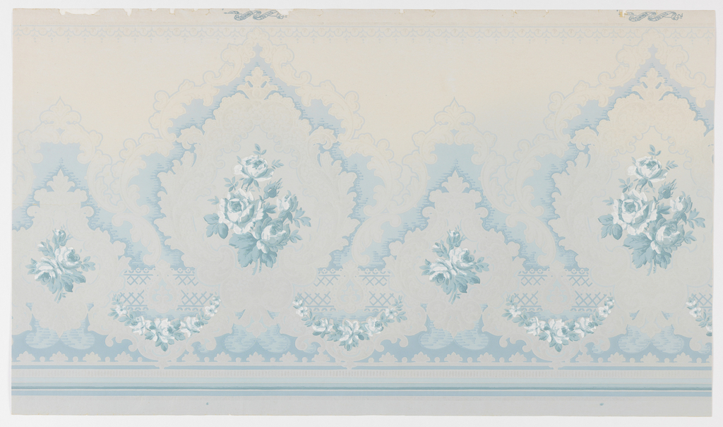 Rose bouquets set within medallions, alternating large and small. Originally part of a matching set of sidewall, frieze and ceiling papers. The background shades from a darker blue at the bottom to a lighter blue at the top. Printed in shades of blue and white on blue ground, with white mica.