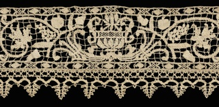 Horizontal panel with design of two angels, confronted, holding a heraldic device with flanking stags. There are two of these groups separated by an urn motif with scrolling oak branches, leaves and acorns. A rampant lion is at either end of the piece. Tabbed border is bobbin lace.