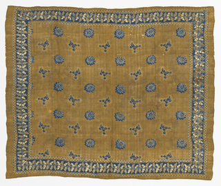 Silk square with tan ground and blue and white design imitating Javanese batik.  Border of chevrons and dots enclosing acorns. Scattered floral motifs of twelve-petaled rosettes and detached bulbous springs of vine in central area.