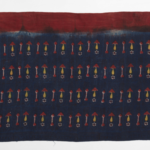 Resist-dyed loosely-woven cotton cloth with four rows of abstracted floral design in red, yellow and white on a dark blue ground. Red boder along one long edge.