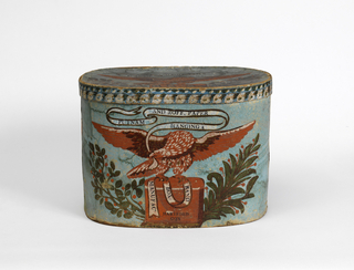 "Bandbox scene depicts eagle bearing in his beak a banderole advertising the manufacturer. Printed on banderole shown in pattern: ""PUTNAM AND ROFF. PAPER/ HANGING &/ BAND/ BOX/ MANUFACR/ HARTFORD/ CON"". Light blue ground block printed in orange, white, gray, and light brown distemper colors, and in green, brown, black and yellow with glossy finish. Rim covered in border paper with blue ground, block-printed in white, pink, brown and green."
