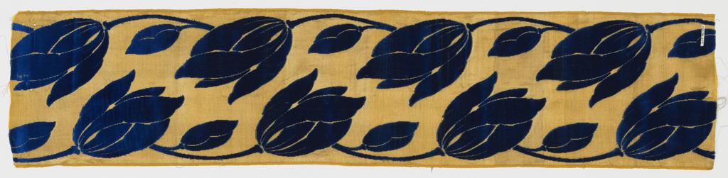 Sample of a wide ribbon with a gold twill ground has a vertical design of two lines of dark blue tulips in cut velvet, one facing up and one facing down. Pile warp cut away in voided areas.