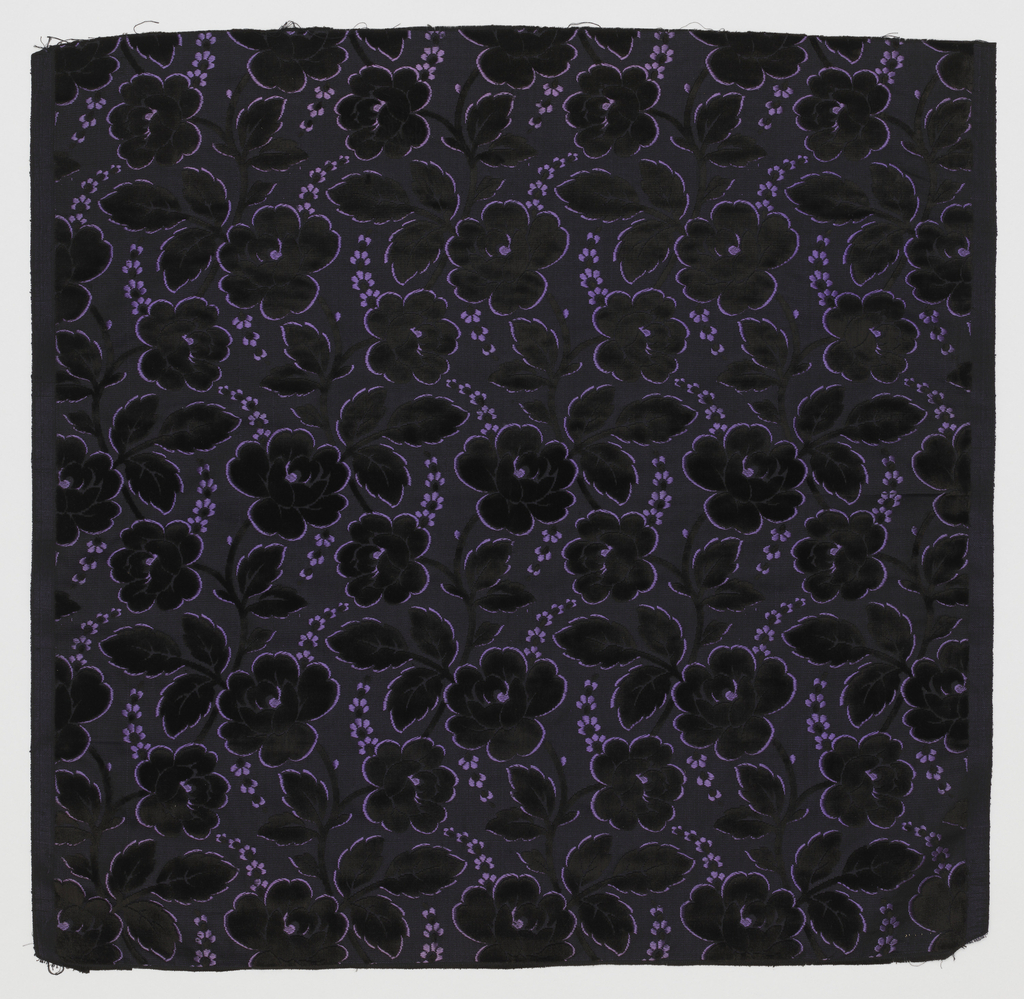 Sample has a design of slender serpentine stems with large stylized roses in black velvet outlined with short floats of secondary silk weft. Sprays of minute flower in the same technique form serpentine lines that connect to flower heads.