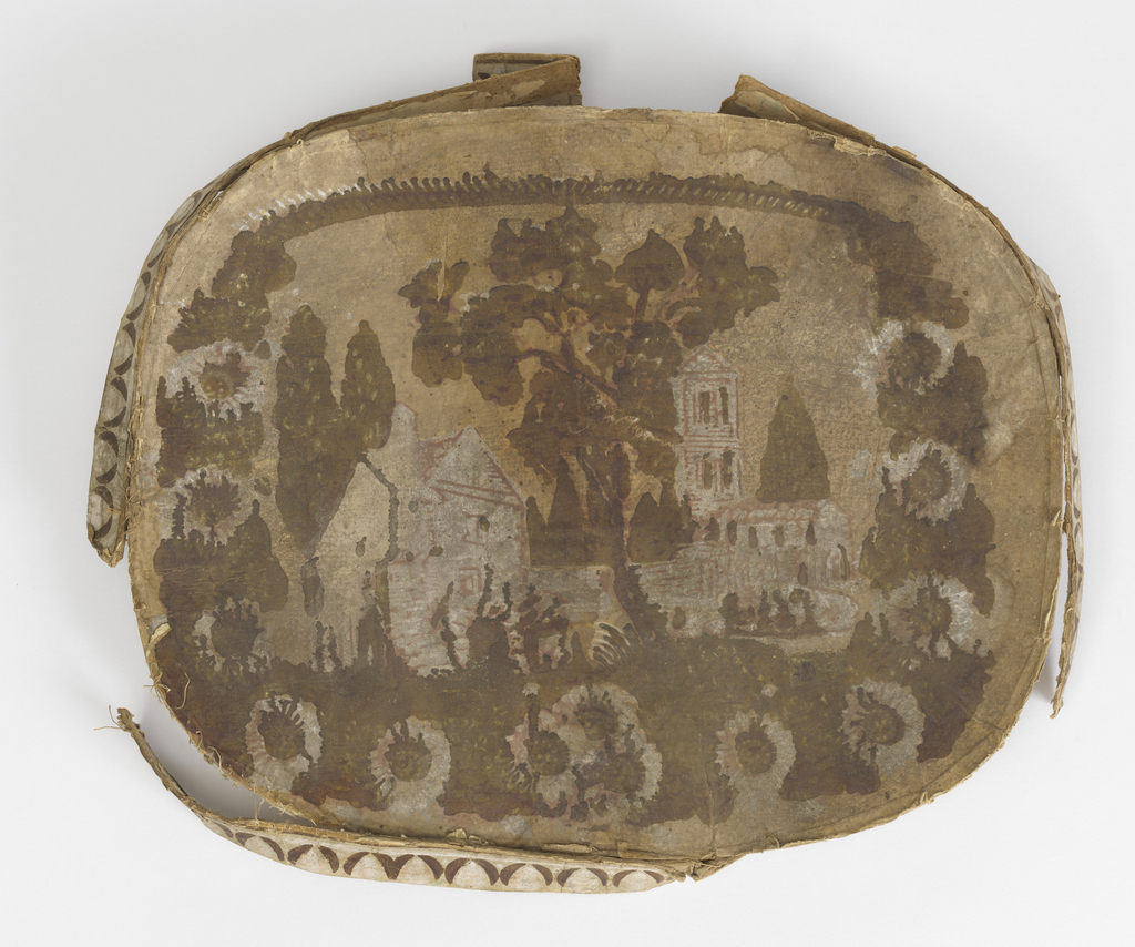 """Pasteboard bandbox lid, rim partially attached. """"Castles in Spain"""" pattern. Buildings, trees, in pink, browns, on yellow background, in enframement of green foliage and white flowers."""