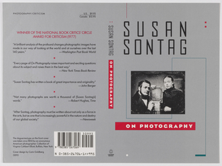 "Book jacket design for ""On Photography,"" part of Susan Sontag series. On gray ground, a black and white photoillustration of a 19th century daguerreotype portrait showing the figures of a man and woman holding a framed family photograph. Surrounding the photoillustration, a winding rectangular line in blue. Author's name in black text above, title in white text within red rectangle below. At spine, author's name in black text, title in white text within red rectangle, publisher's name and colophon (logo) in black at bottom. At back cover, printed text description and excerpts from reviews. Credits at lower left, bar code at lower right."