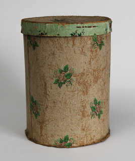 Tall bandbox covered with wallpaper, printed with flowers with bright green leaves. Top of lid covered with matching paper, with rim of top covered in a small floral pattern on light green ground. The green pigment on the wallpaper appears to be arsenic.Manufacturer label pasted inside lid.