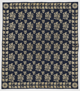 Bedcover in blue and white, reversible double cloth. Pattern of stylized detached flower clusters; border of grape vine design. Star in corner. At one side the date 1828 woven in and letter A.H. (?) – second letter not complete.