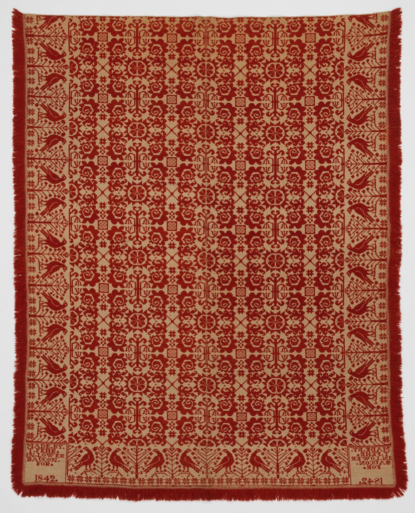 "Coverlet with a design of highly stylized plants forms and stars in red wool on a cream ground. Wide border with birds on either side of a tree. In two corners, marks that read: ""Made by T. Fehr in Lower Saucon for . 1842."""