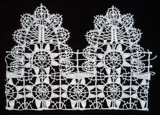 Fragment of provincial lace worked in an older Genoese pattern with oval tabs and geometric star shapes.