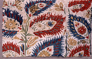 Fragment of embroidery in red, blue, tan, green and cream silk in a floral design.