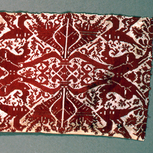 """Linen band embroidered with red silk with a repeating alternation of two patterns. One is a mermaid and the other a bird and cornucopia, each flipped both vertically and horizontally. The bird and cornucopia portion of the design is taken from Vavassore's pattern book """"Esemplario di Lavori,"""" published in Venice in 1532."""