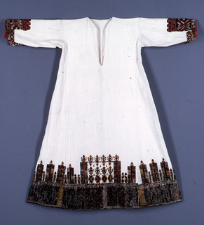 Long dress of heavy white cotton, straight sleeve, body flares slightly at hem as long, wedge-shaped pieces are sewn in from under arm to hem. Ornamented at the hem with a deep border of embroidery in black, brown, olive green and red. Design is highly stylized: at bottom, solidly worked from 6 3/4 inches in narrow bands of zigzag patterns; above, an arrangement of pillar-like forms and stylized plants, with a plant at the top of each pillar, so that the whole suggests a wall. Height of the whole border is 14 inches. Cuffs of sleeves are also finished with a deep border of embroidery in brown, red, white and yellow silks, in geometric forms. Mainly cross stitch; on sleeve coarse darning stitch.