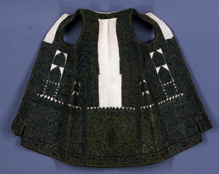 Woman's white wool vest, elaborately embroidered in highly stylized vine patterns. Motif of pointed leaf suggesting ogive. Wide, solidly worked band around hem, around arm holes and down back.