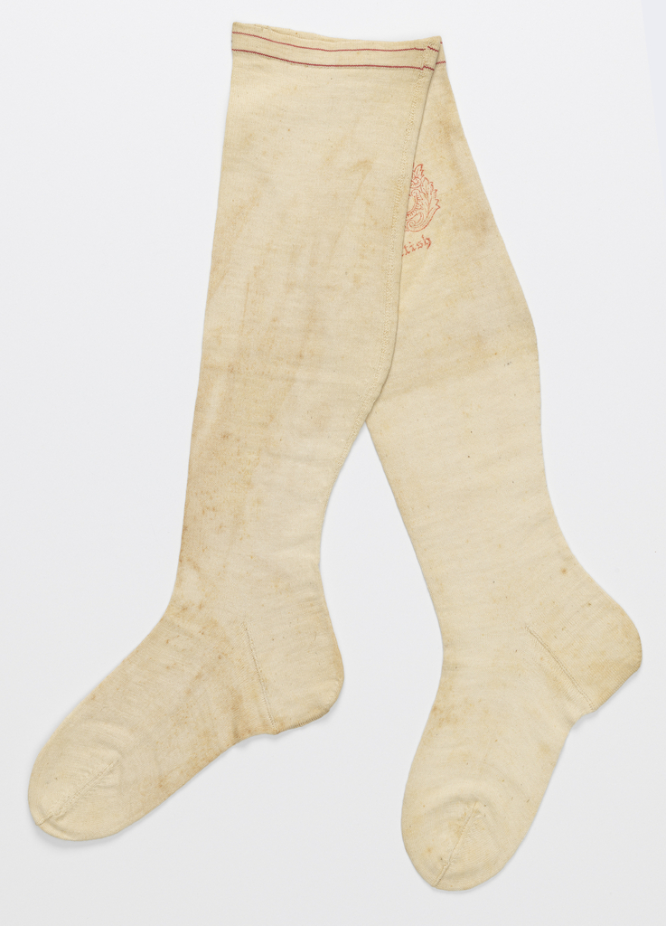 "Pair of white knee length stocking. Two narrow red lines at top. Red stamp on one: ""Superior Manufacture Sea-Island Cotton Three Thirds."""