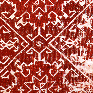 Rectangle of off-white linen embroidered in red silk in an allover pattern of interlocking diamonds containing eight-pointed stars. The background is embroidered in red; the design is reserved in the linen ground.