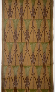 Repeating motif of an ear of wheat or other grain. Each ear is cut flush across the top with scrolling foliage on either side of the stem. The grain motifs are in relief against a textured, swirled background. Printed in green and brown then hand-rubbed to simulate leather.