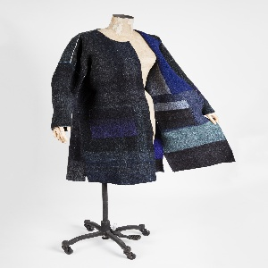 Long-sleeved, knee-length, reversible coat in neelde-punched felt made from recyled sweaters. One side is a dark irregular plaid of blacks and blues, the other a patchwork of blue-tone knit fabrics.