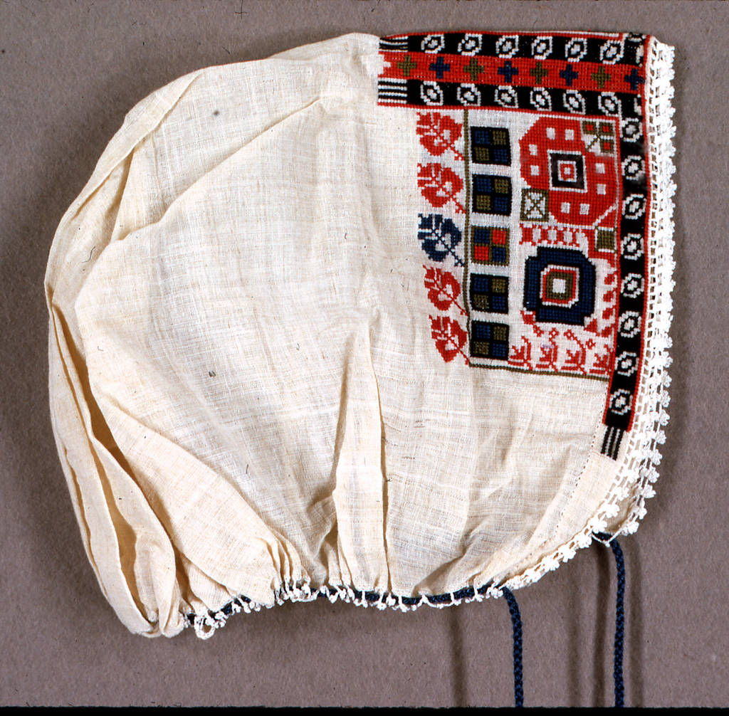 Woman's cap of white cotton embroidered in a wide band across teh fron in red, green and blue, in stylized leaf and geometric forms. Gathered at bottom with a blue cord.