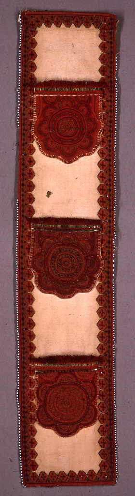 Band of ivory linen bordered with wool embroidery in two shades of red, black and metallic gold with copper sequins. Three applied, embroidered pockets embroidered in the same materials in a pattern of concentric circles. Entire band edges in black and white beading.