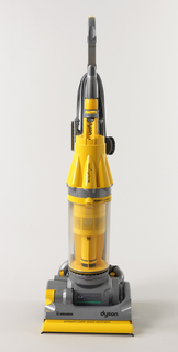 Upright vacuum cleaner: metalic gray, yellow, and clear housing leading up to handle, with cavities for tools (brushes, tubes); front dominated by motor and dust collection bin assembly of yellow and clear plastic; at bottom, wide, low cleaning head with brush in front, two wheels in back, yellow at joints and adjustment points. Power cord wraps around back of handle.