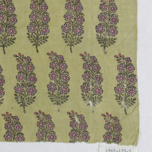 Fragment of block printed cotton in red, purple and dark green on yellow-green background. Allover pattern of stylized floral branch.