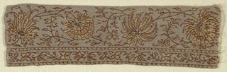 Horizontal repeat of four different large flowerheads on fine scrolling stems with tiny leaves. Guard band with scrolling flowers and leaves with decorated guard strip above and below. In golden tan and dark brown with reddish brown outlines and touches of white on greyish tan ground. Reinforced long sides; plain selvedge on one end.