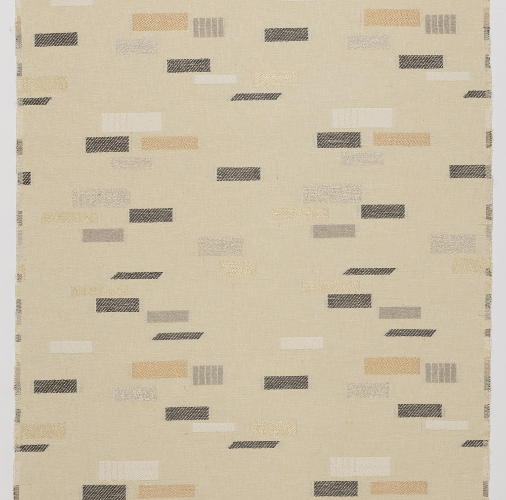 Length of woven textile with an off-white ground and irregular squares and rectanges in different twill weaves and different fibers, in ivory, copper, gray, and dark brown.