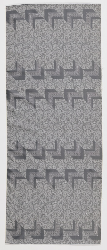 Length of gray silk with a woven paisley design on the diagonal, for the purpose of making men's ties.
