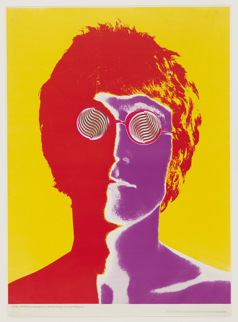 A depiction of the head and shoulders of musician John Lennon on vibrant yellow ground. The left side of image and hair saturated in bright orange-red; the right side of image in deep purple. The features are visible as in a photographic negative with negative areas highlighted in bright white. Superimposed on the face, a pair of round glasses with lenses formed by bright orange, green, and white spirals.