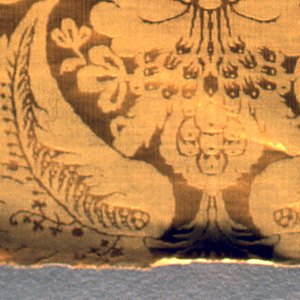 Yellow silk damask with striae effect in a large-scale pattern of symmetrical floral clusters and curving leaves. Possible a reproduction of a seventeenth-century textile.