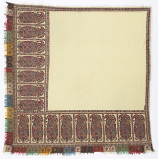 Square Kashmir shawl with a design of cones primarily in reds, with an open ivory field. Each cone is 10 1/2 inches high, and is compartmented by a narrow border of floral vines. Currently the shawl has wide borders on two adjacent sides and narrow borders on the two remaining sides. It has been re-made from fragments of a long shawl. Originally each end would have had a wide border nine cones in width: one side of the square version has the full nine cone pattern, the other has seven cones. The two remaining cones exist as a separate fragment (1958-148-5b). The narrow guard border of a similar floral vine has been stitched to the two remaining sides. In this way the shawl could be folded diagonally to form the triangular shawl popular in the mid-19th century.