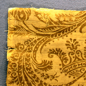 Short panel of yellow damask with symmetrical design of foliage, flowers and a crown.