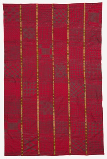 Wrapper composed of six strips of bright red cotton stamp-printed in dark brown/black in a variety of geometric symbols. The strips are joined by embroidery patterned in bands of black, blue, green, and yellow.