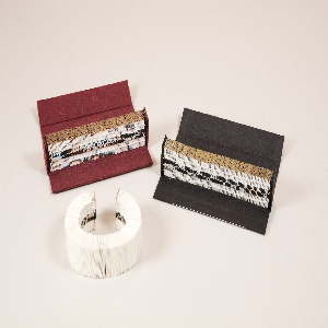 """Red box containing process objects associated with the """"Rembrandt's Hands and a Lion's Paw"""" book bracelet, box and case: white paper bracelet prototype, gilded bracelet prototype, black cardboard box, gilded bracelet prototype with gold clasps, red cardboard box"""