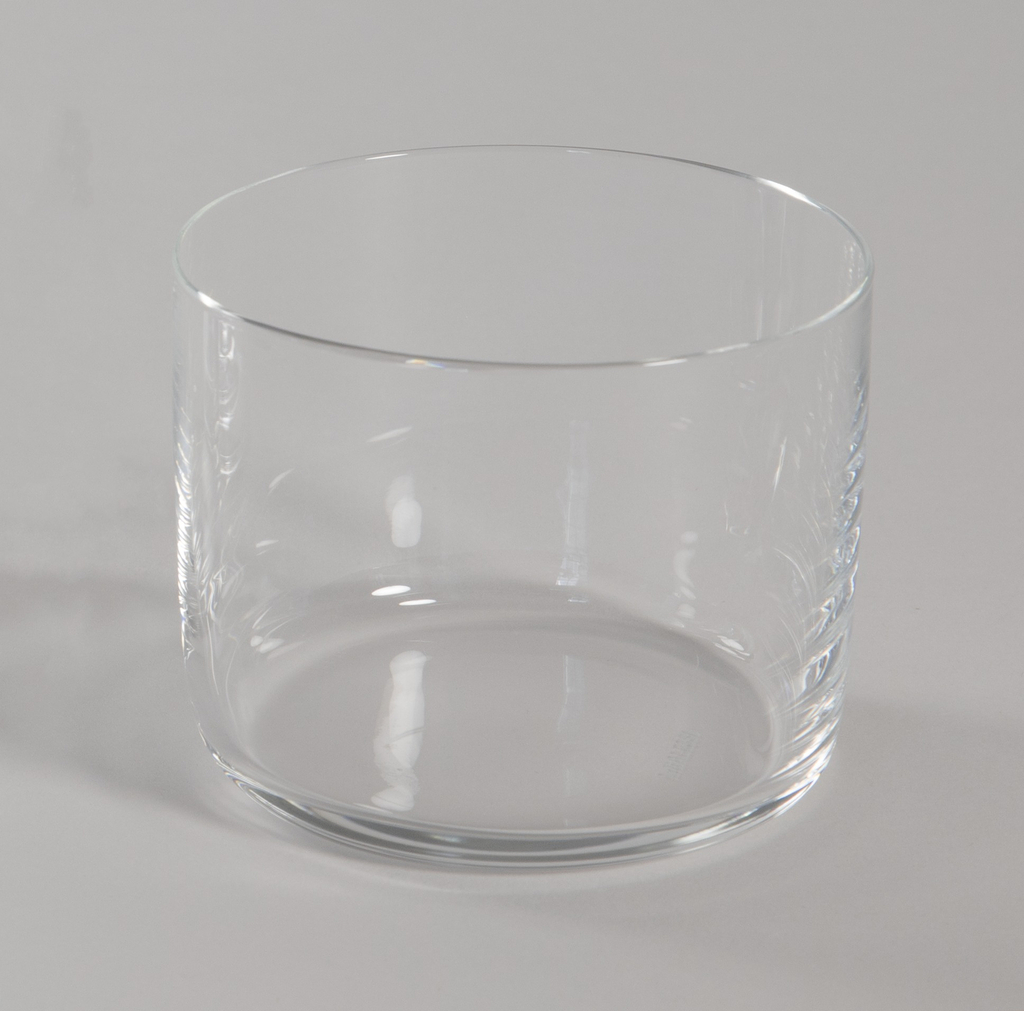 Stemless red wine glass of crystalline glass with curved edges at base and straight sides.