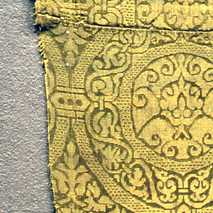 Yellow-green damask lattice of circles connected by a bracket. Each circle contains a flowering plant within a foliate wreath with a circle with octagonal points within a floral scroll wreath. Each concave diamond has a medallion with leaves extended into the four points.