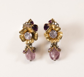 Pair of floral earrings with rhinestone centers and clusters and drops of purple and clear stones with