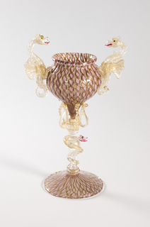 Two gold-flecked seahorses mounted on a chalice with spiral twists in pink and gold; the stem entwined with a serpent; the base matching the chalice with pink and gold reticello decoration